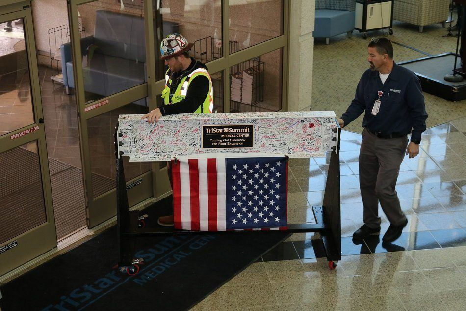Two workers roll out the final steel beam, which is white and covered in staff signatures